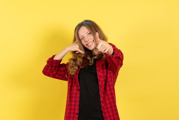 Vista frontale giovane femmina in camicia a scacchi rossa in piedi e in posa su sfondo giallo ragazza colore donna modello umano