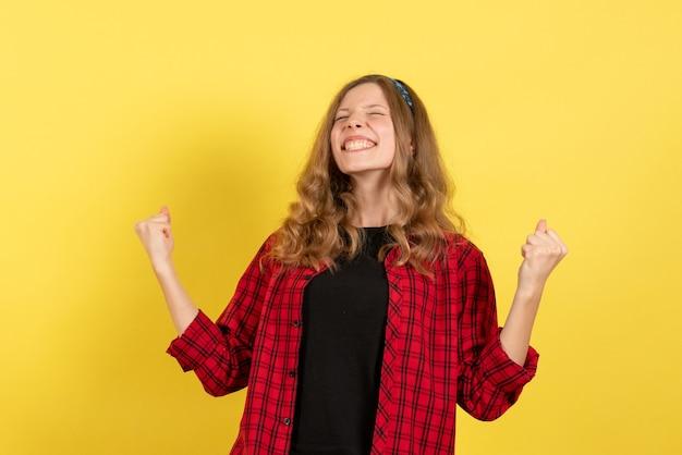 Vista frontale giovane femmina in camicia a scacchi rossa in piedi e gioia su sfondo giallo ragazze modello di colore umano donna