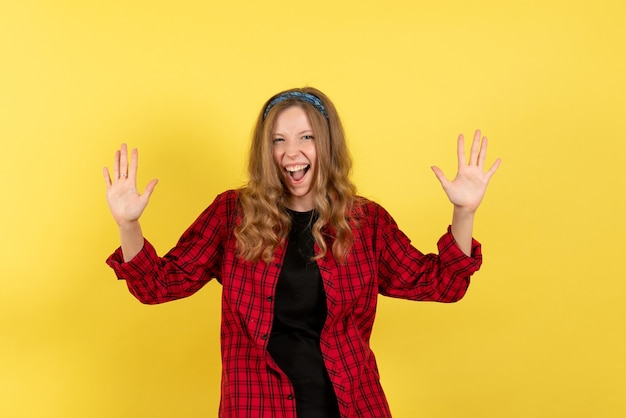 Front view young female in red checkered shirt standing and screaming on yellow background color woman model human girl