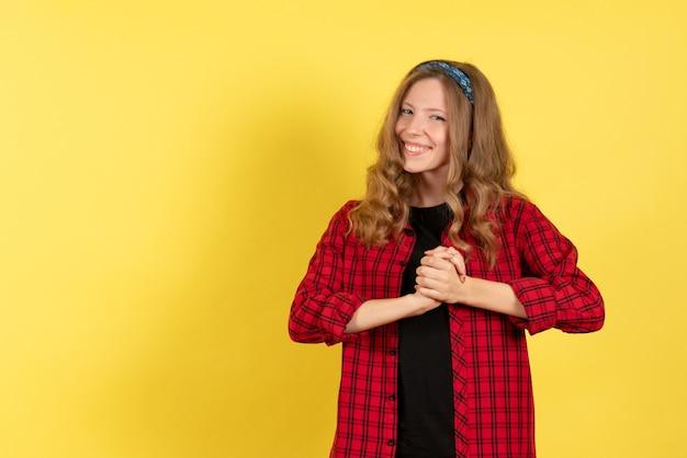 Vista frontale giovane femmina in camicia a scacchi rossa in piedi e sorridente su sfondo giallo colore donna modello umano ragazza