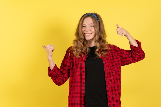 Front view young female in red checkered shirt standing and smiling on yellow background girl color woman model human