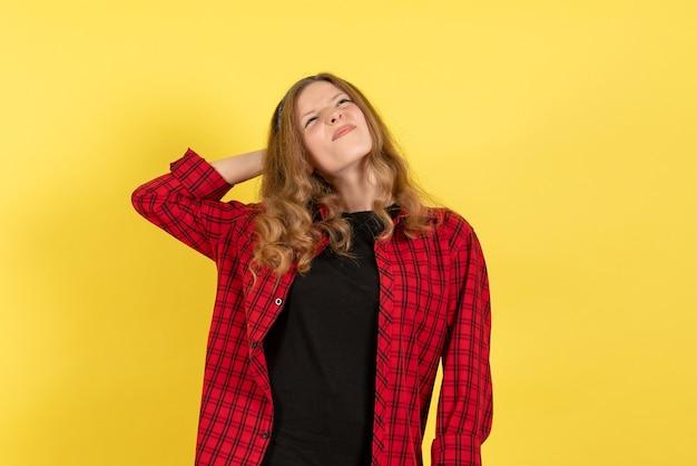 Vista frontale giovane femmina in camicia a scacchi rossa in piedi e pensare su sfondo giallo colore donna modello umano ragazza