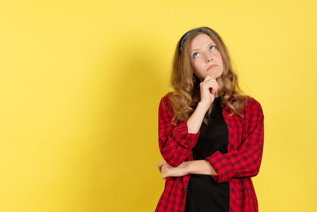 Vista frontale giovane femmina in camicia a scacchi rossa in piedi e pensare su sfondo giallo ragazze donna modello di colore umano