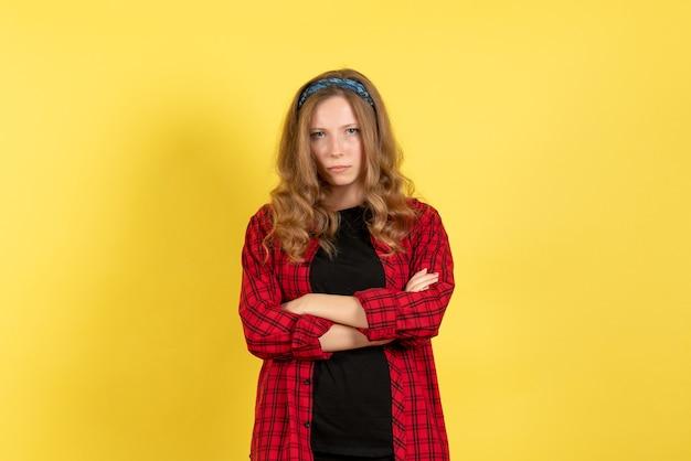Vista frontale giovane femmina in camicia a scacchi rossa in piedi con espressione pazza su sfondo giallo ragazza colore donna modello umano