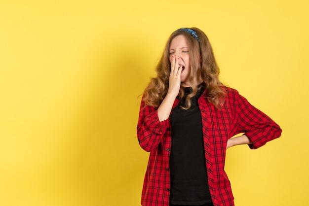 Vista frontale giovane femmina in camicia a scacchi rossa in piedi e sbadigliando su sfondo giallo ragazza colore donna modello umano