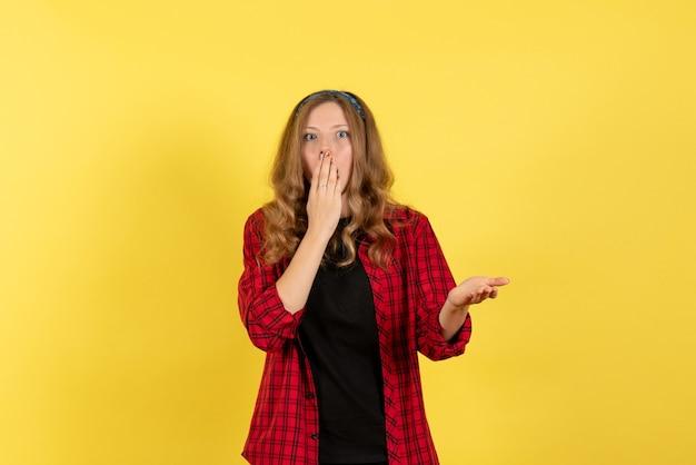 Vista frontale giovane femmina in camicia a scacchi rossa in piedi su sfondo giallo ragazze modello di colore umano donna