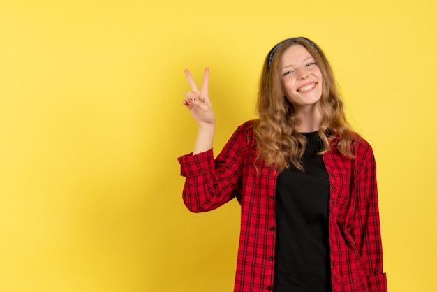 Vista frontale giovane femmina in camicia a scacchi rossa in piedi su sfondo giallo ragazze donna modello di colore umano