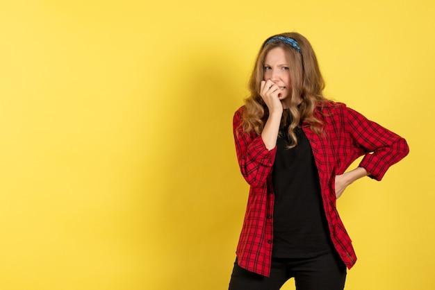 Giovane femmina di vista frontale in camicia a scacchi rossa che sta sulla donna di modello di colore umano delle ragazze dello scrittorio giallo