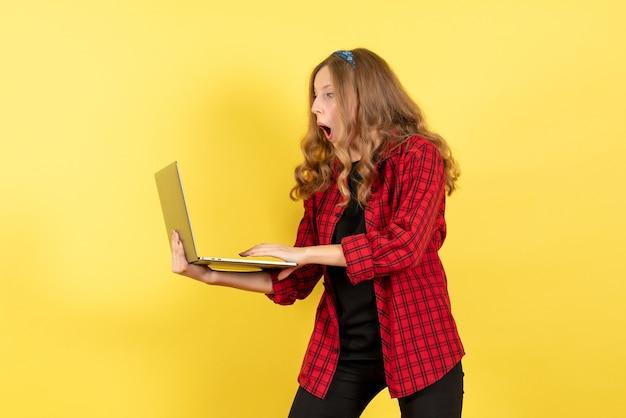 Vista frontale giovane femmina in camicia a scacchi rossa utilizzando il suo computer portatile su sfondo giallo donna emozione umana modello moda ragazza