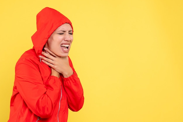 Front view young female in red coat having sore throat on yellow background