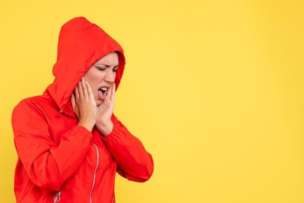 Vista frontale giovane femmina in cappotto rosso con mal di denti su sfondo giallo