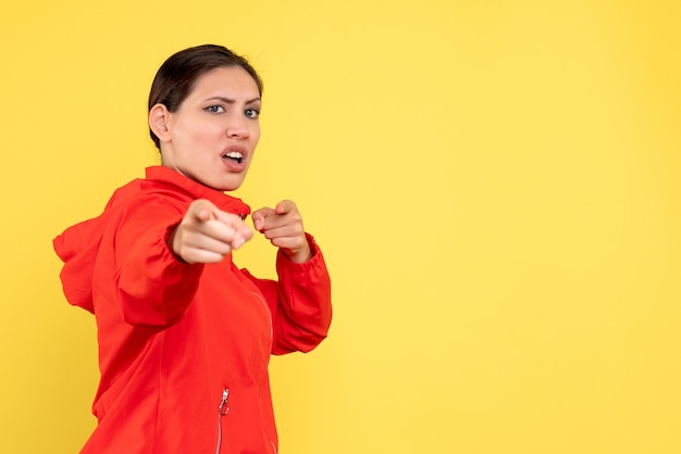 Front view young female in red coat on yellow background