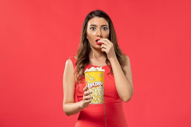 Giovane femmina di vista frontale in camicia rossa che mangia popcorn che guarda film sullo scrittorio rosso