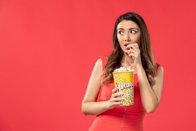Giovane femmina di vista frontale in camicia rossa che mangia popcorn guardando film sulla superficie rossa