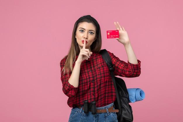 Giovane femmina di vista frontale in camicia rossa che tiene la carta di credito sul colore della donna umana di sfondo rosa