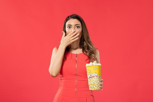Giovane femmina di vista frontale in camicia rossa che tiene popcorn sullo scrittorio rosso-chiaro