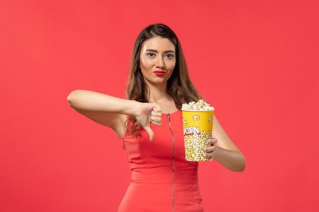 Giovane femmina di vista frontale in camicia rossa che tiene popcorn sulla superficie rosso chiaro