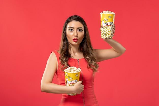 Giovane femmina di vista frontale in camicia rossa che tiene i pacchetti di popcorn sulla superficie rossa