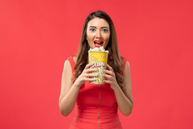 Giovane femmina di vista frontale in camicia rossa che tiene popcorn sullo scrittorio rosso