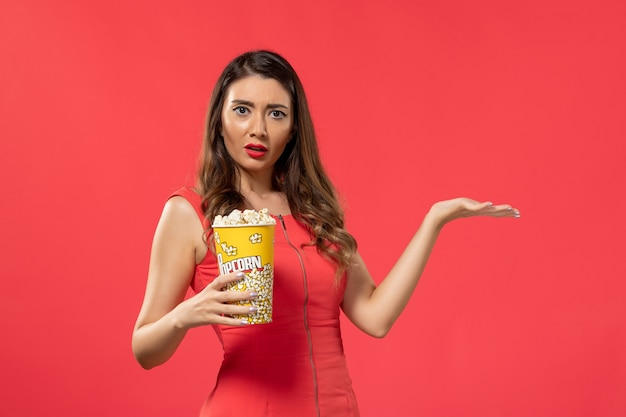 Front view young female in red shirt holding popcorn on red surface