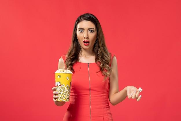 Giovane femmina di vista frontale in camicia rossa che tiene popcorn sulla superficie rossa