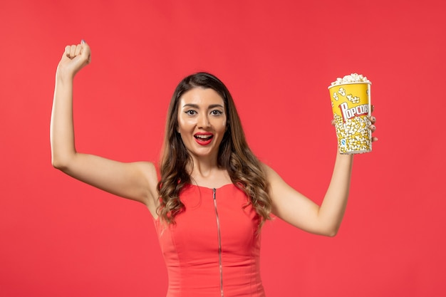 Front view young female in red shirt holding popcorn and rejoicing on red surface