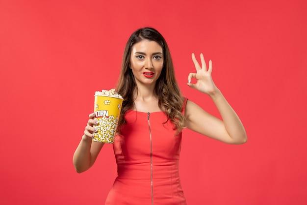Giovane femmina di vista frontale in camicia rossa che tiene popcorn e sorridente sulla superficie rossa