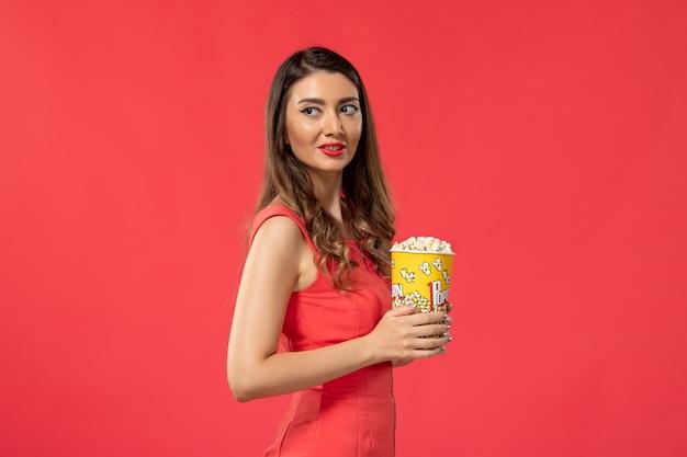 Giovane femmina di vista frontale in camicia rossa che tiene popcorn guardando film sulla superficie rossa