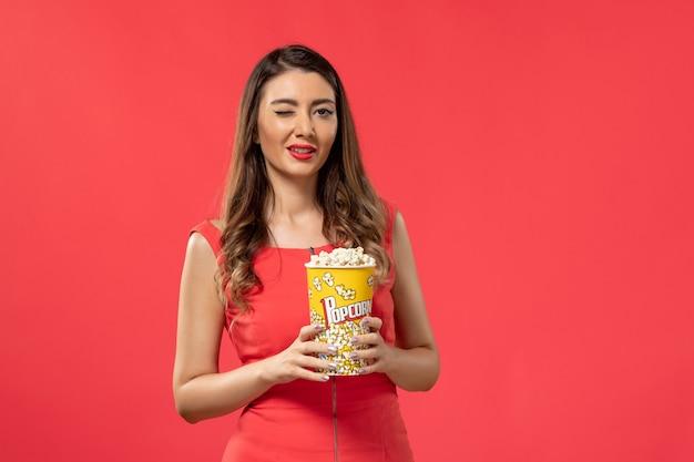 Giovane femmina di vista frontale in camicia rossa che tiene popcorn guardando film che sbatte le palpebre sulla superficie rossa