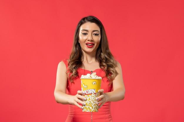 Giovane femmina di vista frontale in camicia rossa che tiene popcorn con l'espressione eccitata sulla superficie rossa