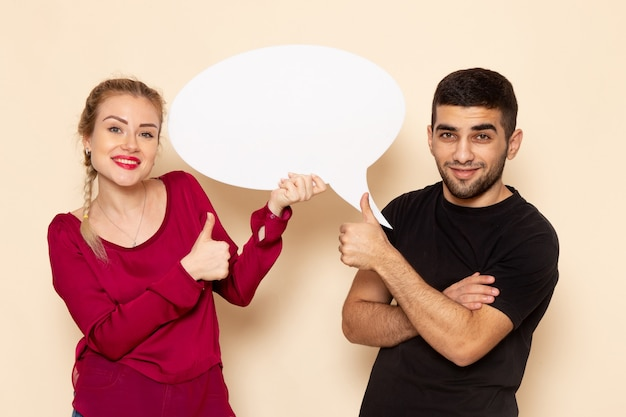 Front view young female in red shirt holding white sign with man on the cream space female cloth  photo violence domestic