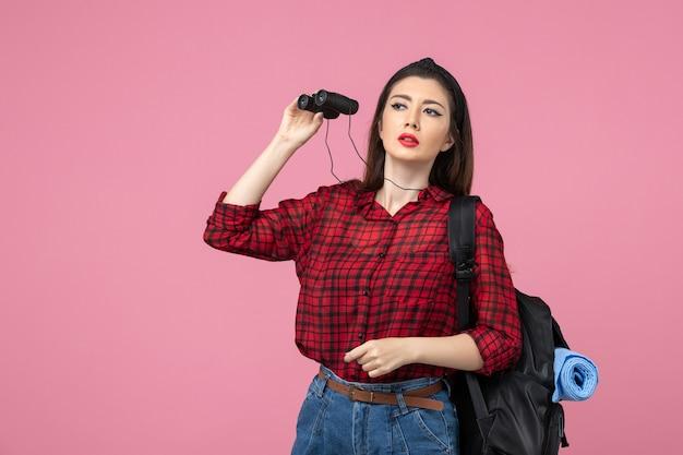 Vista frontale giovane femmina in camicia rossa utilizzando il binocolo su sfondo rosa studente colore donna