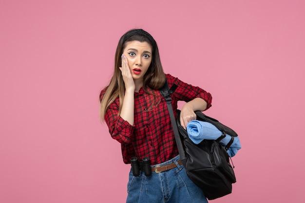 Giovane femmina di vista frontale in camicia rossa con il sacchetto sul modello rosa della foto della donna dello scrittorio