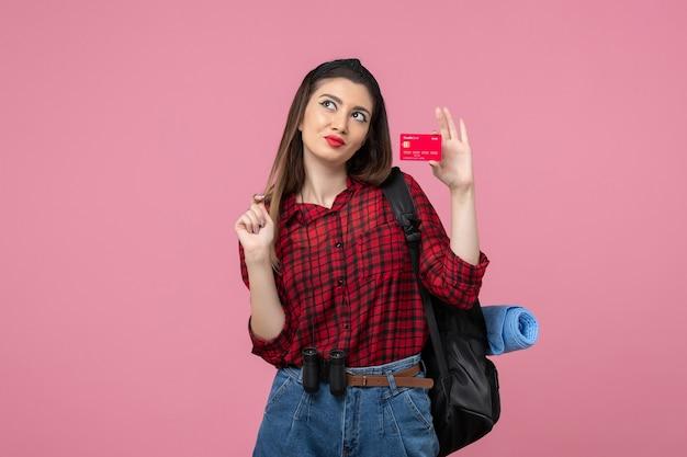 Vista frontale giovane femmina in camicia rossa con carta di credito su sfondo rosa chiaro donna colore umano