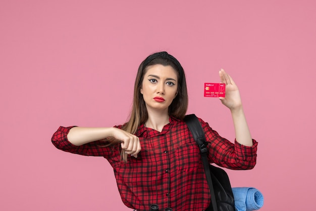 Front view young female in red shirt with bank card on a pink background human woman color