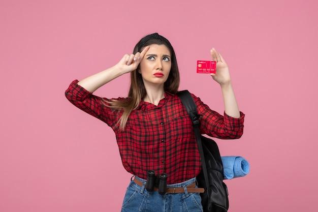 Vista frontale giovane femmina in camicia rossa con carta di credito su sfondo rosa colore della donna umana