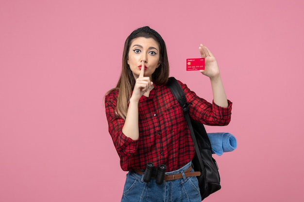 Front view young female in red shirt with bank card on a pink background woman color human