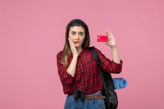 Vista frontale giovane femmina in camicia rossa con carta di credito sullo sfondo rosa donna colore umano
