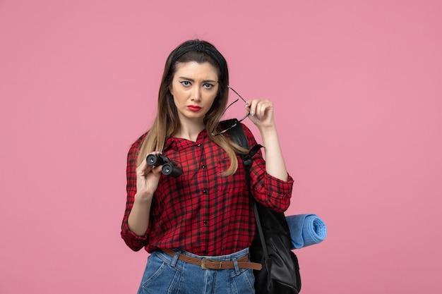 Giovane femmina di vista frontale in camicia rossa con il binocolo sul modello di colore della donna del fondo rosa chiaro