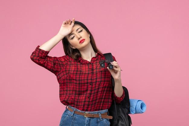 Giovane femmina di vista frontale in camicia rossa con il binocolo sulla donna di modo di colore di sfondo rosa