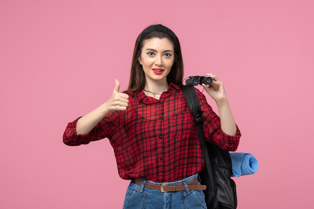 Front view young female in red shirt with binoculars on pink background fashion color woman