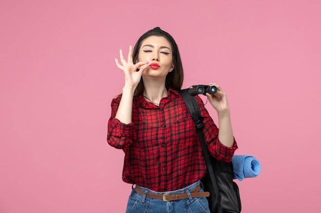Giovane femmina di vista frontale in camicia rossa con il binocolo sulla donna di colore di moda sfondo rosa