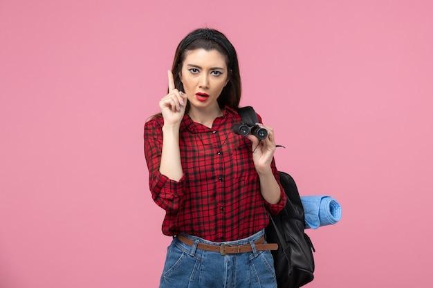 Giovane femmina di vista frontale in camicia rossa con il binocolo sulla donna di colore dello studente di sfondo rosa