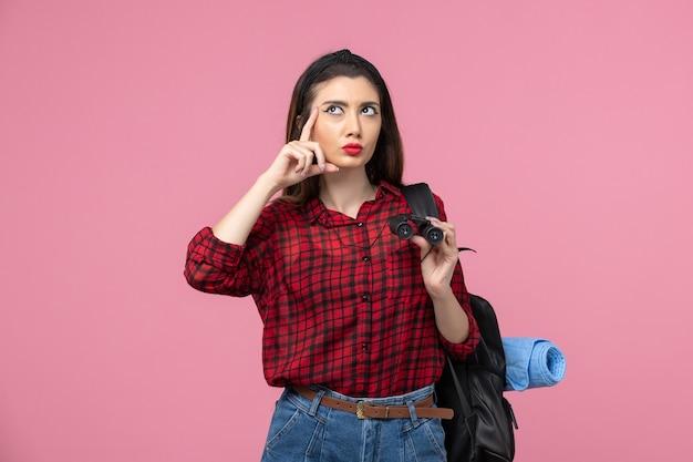 Vista frontale giovane femmina in camicia rossa con il binocolo su sfondo rosa studente colori donna