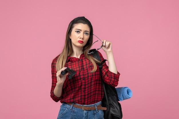 Giovane femmina di vista frontale in camicia rossa con il binocolo sul modello di colori della donna del fondo rosa