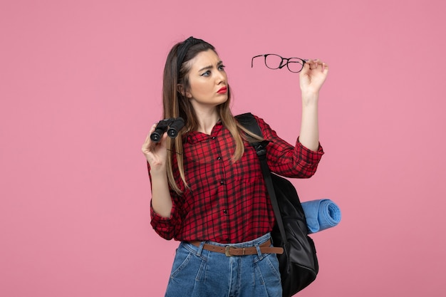 Front view young female in red shirt with binoculars on a pink background woman photo model