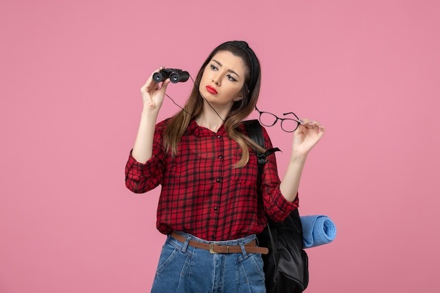 Front view young female in red shirt with binoculars on the pink background woman photo model
