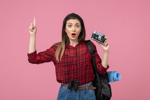 Front view young female in red shirt with camera on a pink background photo woman model