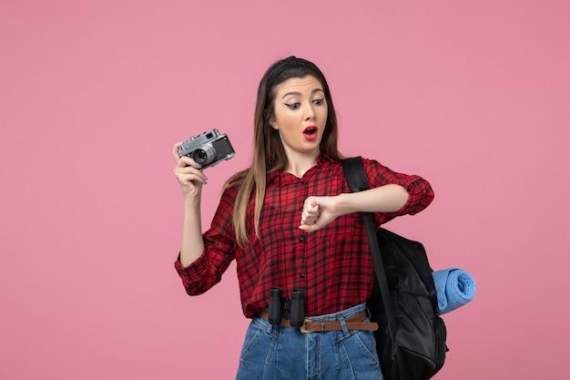 Giovane femmina di vista frontale in camicia rossa con la macchina fotografica sulla foto di modello della donna del fondo rosa