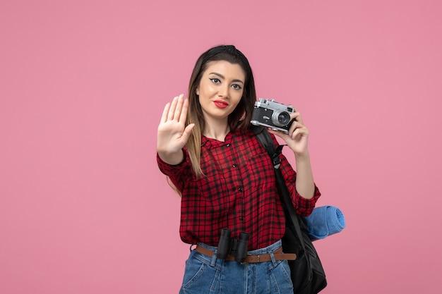 Giovane femmina di vista frontale in camicia rossa con la macchina fotografica sul modello rosa della donna della foto dello scrittorio